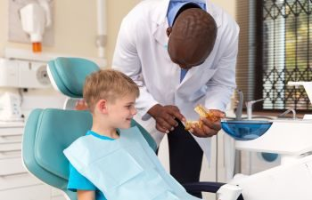 the child is sitting on the dentist's chair and the doctor shows him a tooth model